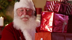 Santa Claus peeks out from behind stack of gifts Stock Footage
