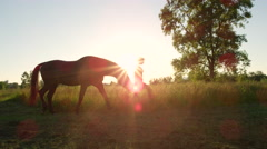 CLOSE UP: Big stallion horse pasturing while on a walk with a girl at sunset Stock Footage