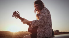 Young Couple Sitting On Car Playing Guitar Singing Road After Sunrise Or Sunset Stock Footage