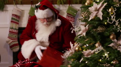 Santa Claus puts gifts under tree on Christmas Eve Stock Footage