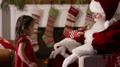 Little girl sits with Santa Claus Stock Footage