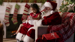 Santa Claus shows little girl a snow globe Stock Footage
