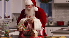 Santa Claus in kitchen decorating gingerbread house Stock Footage