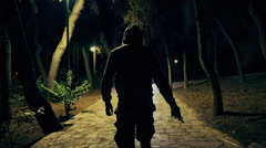 Hooded man walks in dark park draws knide,slomo 100p Stock Footage