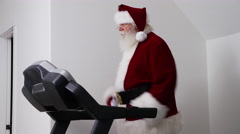 Santa Claus running on treadmill in gym Stock Footage