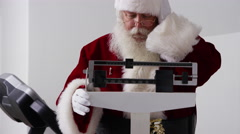 Santa Claus looks at weight on scale Stock Footage