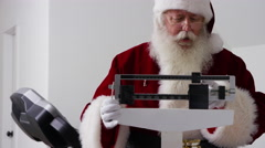 Santa Claus upset to see weight on scale Stock Footage