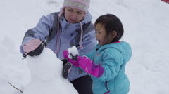 Mother and daughter building snowman together Stock Footage