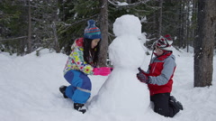 Two children building snowman together Stock Footage