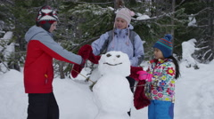 Mother and children building an snowman together Stock Footage