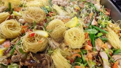 Closeup on chicken wok, with vegetables and noodles, at a restaurant kitchen Stock Footage