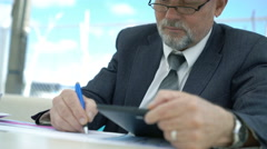 Imposing old man writing down from tablet in cafe. 4K Stock Footage