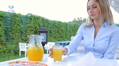 Blond woman pouring juice in a glass and drinks Stock Footage