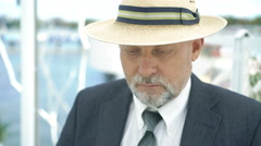 Elderly man in hat putting on glasses and nodding on camera. 4K Stock Footage