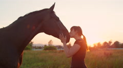 CLOSE UP: Smiling young woman cuddling and caressing her best friend horse Stock Footage