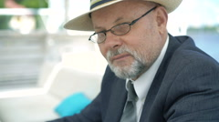 Portrait of eldery man in hat and glasses smiling and nodding on camera. 4K Stock Footage