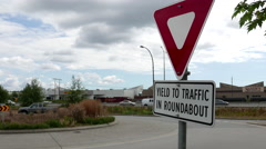 Motion of yield to traffic in roundabout sign with traffic flow background Stock Footage