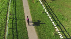 AERIAL: Woman horseback riding powerful gelding on horse ranch on sunny day Stock Footage