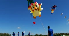 The person controls the kite, a big yellow parrot hovering in the sky,festival Stock Footage