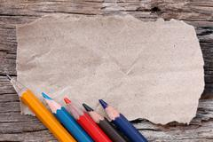 Colored pencils or Crayons and brown cardboard on old wooden floor. Stock Photos