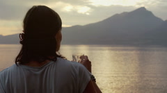 Woman with flower drinking water and standing next to the sea Stock Footage