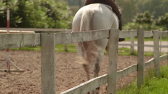 Girl riding on a horse arena on the outside in the country back shot Stock Footage