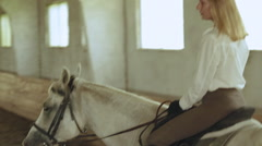 The girl rides a horse at the indoor arena Stock Footage