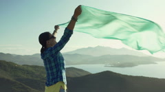 Happy woman holding blue scarf which is moving on the wind, steadycam shot Stock Footage