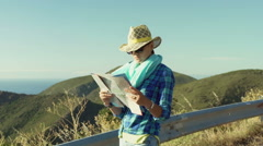 Woman standing on the hill and reading a map, steadycam shot Stock Footage