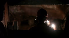 Silhouette of miner descends into a mine shaft Stock Footage