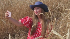 Beautiful girl photographed themselves use a smartphone sitting in a wheat field Stock Footage