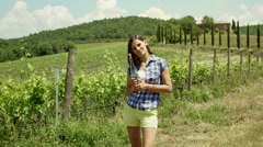 Woman holding bottle of wine and smiling to the camera, steadycam shot Stock Footage