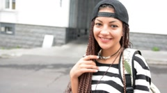 Young woman with dreadlocks put on the cap and walk by street Stock Footage