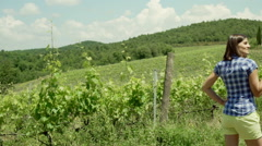 Woman drinking wine while standing a next to the vineyard, steadycam shot Stock Footage