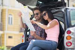 Happy tourist man and woman in car Stock Photos