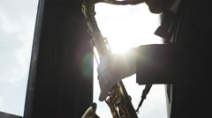 Musician is playing on saxophone near window Stock Footage