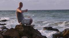 A Young Man Sitting on the Beach With a Laptop on the Rocks and Make Stock Footage