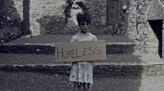"""4k Horror Shot of an Abandoned Child Holding """"Homeless"""" on cardboard Stock Footage"""