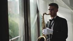 Elegant musician is playing on saxophone near window. 4K Stock Footage