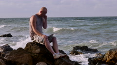 A Young Man Sitting on the Beach With a Laptop on the Rocks and Speak Phone. Stock Footage
