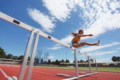 Female Athlete Clearing Hurdles Stock Photos
