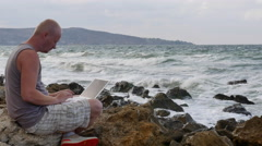 A Young Man Sitting on the Beach With a Laptop on the Rocks. the Waves Beat Stock Footage