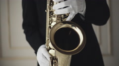 Musician's hands in white gloves, musician is playing on saxophone. Close up Stock Footage