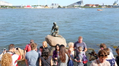 A crowd of tourists are visiting the little mermaid Stock Footage