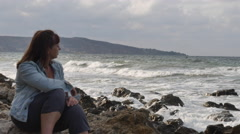 Young Woman Sitting on the Rocky Coast and Misses. Strong Waves Beating Against Stock Footage