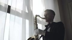 Musician is playing on saxophone near window. 4K Stock Footage