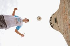 Boy Heading Football In Front Of Old Brick Wall Stock Photos