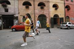 Boys Running With Soccer Ball In Street Stock Photos