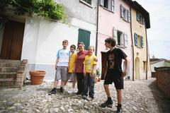 Senior Woman And Four Boys Posing In Street Stock Photos