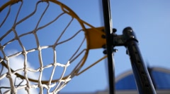 Thrown ball flies right into the basketball hoop on outdoors playground Stock Footage